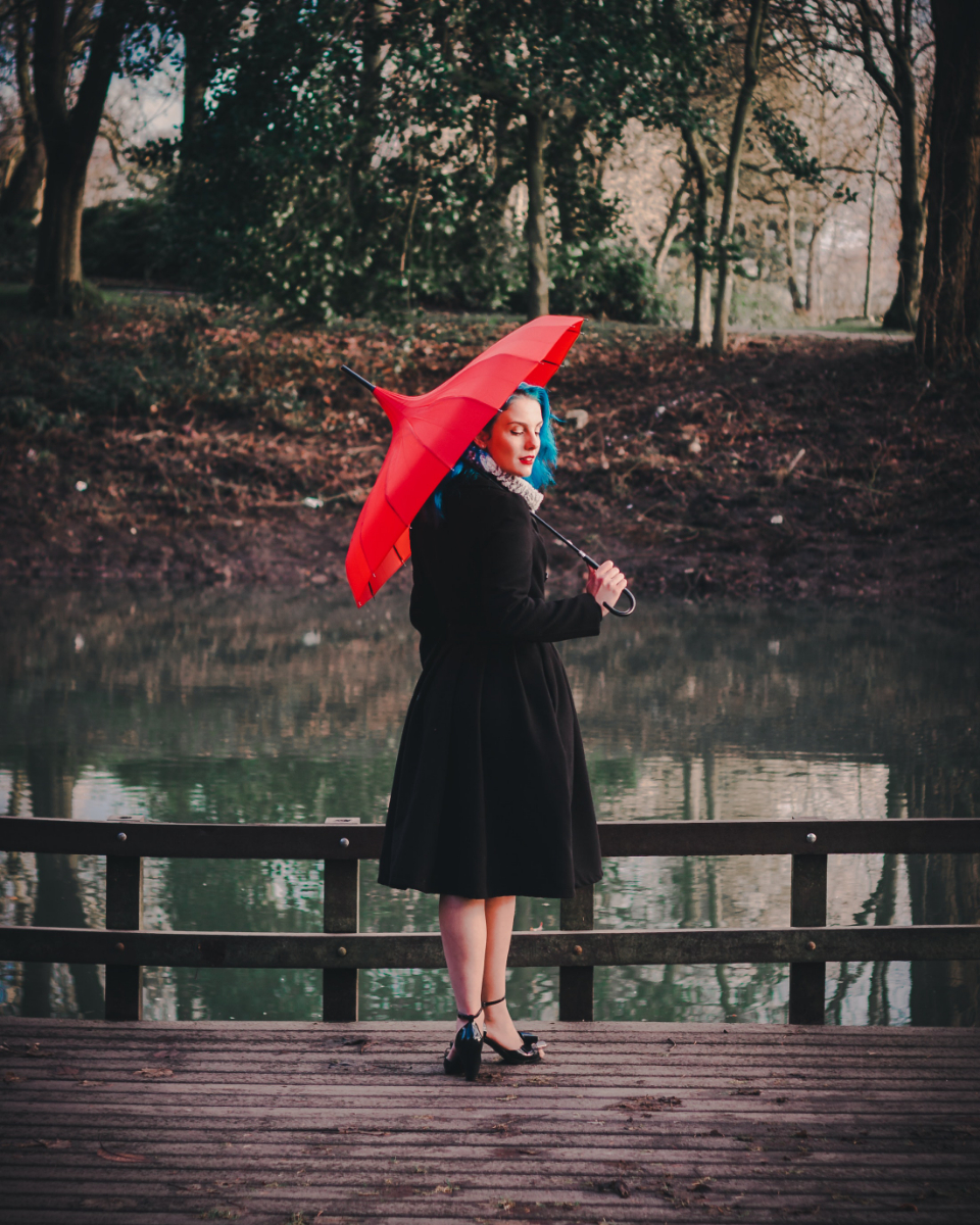 woman red umbrella black dress dress elegant smart look heels reflection water lake river bridge pier wood boards trees