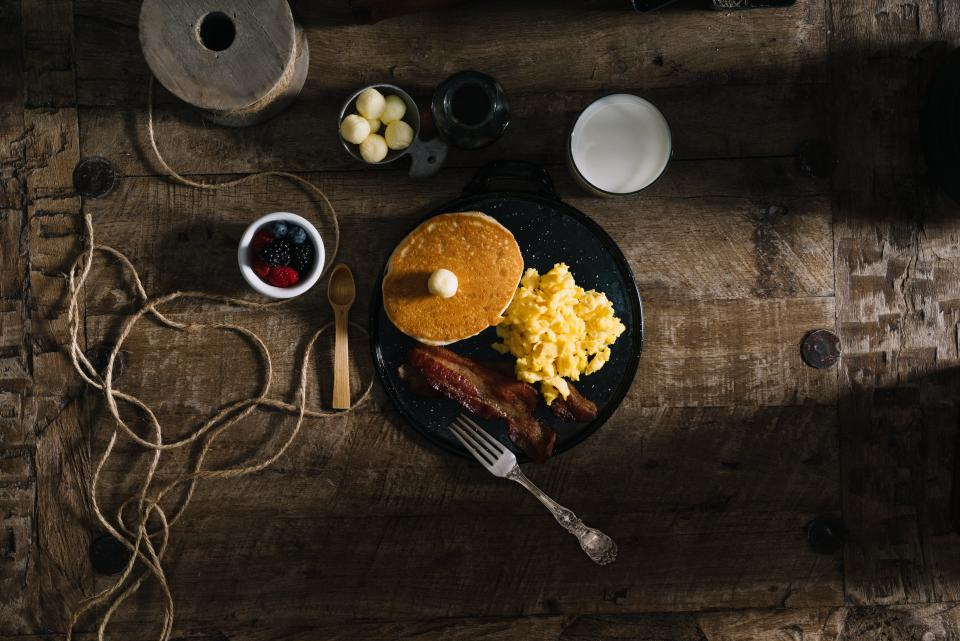 food eat breakfast pancakes eggs bacon berries blueberries raspberries strawberries rope milk top view table spread light shadows