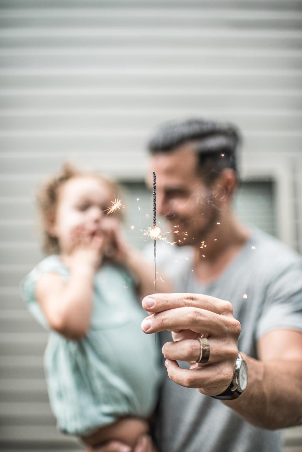 people parent man father carry daughter kid baby child hand stick sparkle light ring watch blur