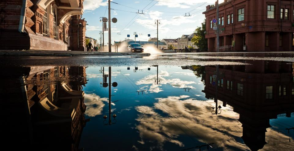 architecture buildings city downtown power electrical lines car flood water puddle reflection splash sky clouds urban metro