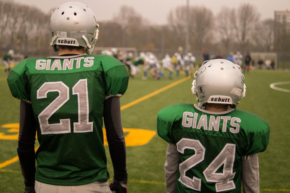 football teammates giants field sports athletes uniform helmets green