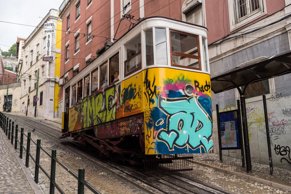 tramcar streetcar trolley lisbon graffiti cobblestone buildings city