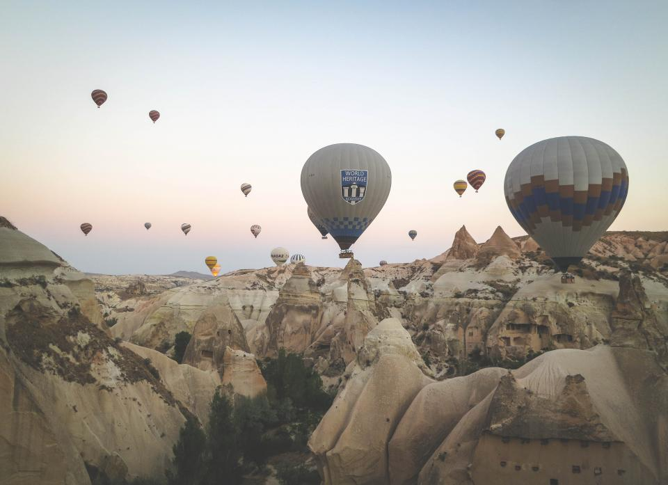 hot air balloons Cappadocia Turkey rocks cliffs valleys