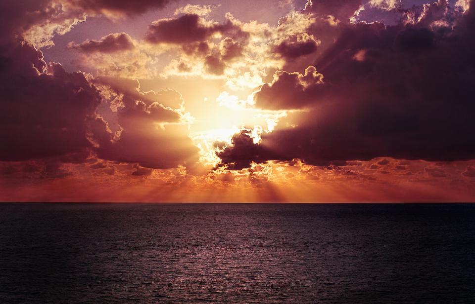 sunset dusk sunbeams sun rays clouds cloudy horizon ocean sea water