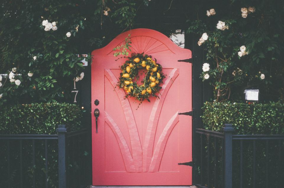 pink red door wreath flowers plants bushes railing entrance house