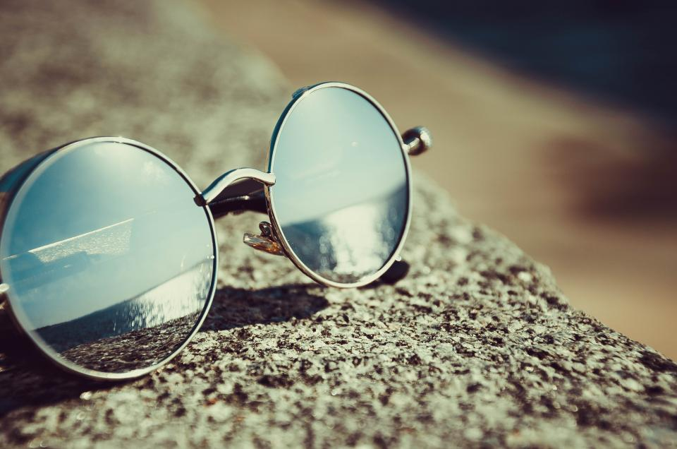 sunglasses reflection summer beach bokeh. blur eyewear rock adventure travel trip vacation