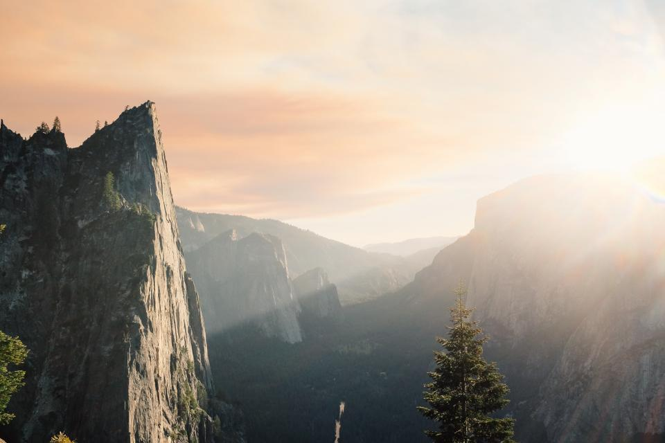 mountains sunlight sunny clouds sunrays cliffs nature trees rocks outdoors peaks valleys