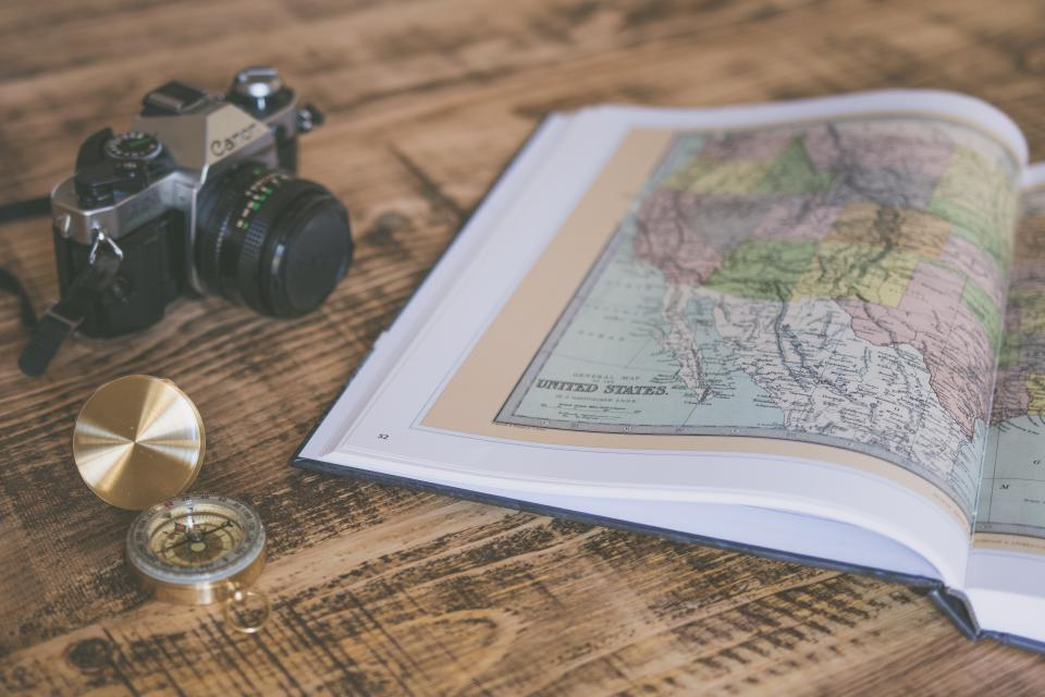 book map geography compass travel camera photography blur wooden table