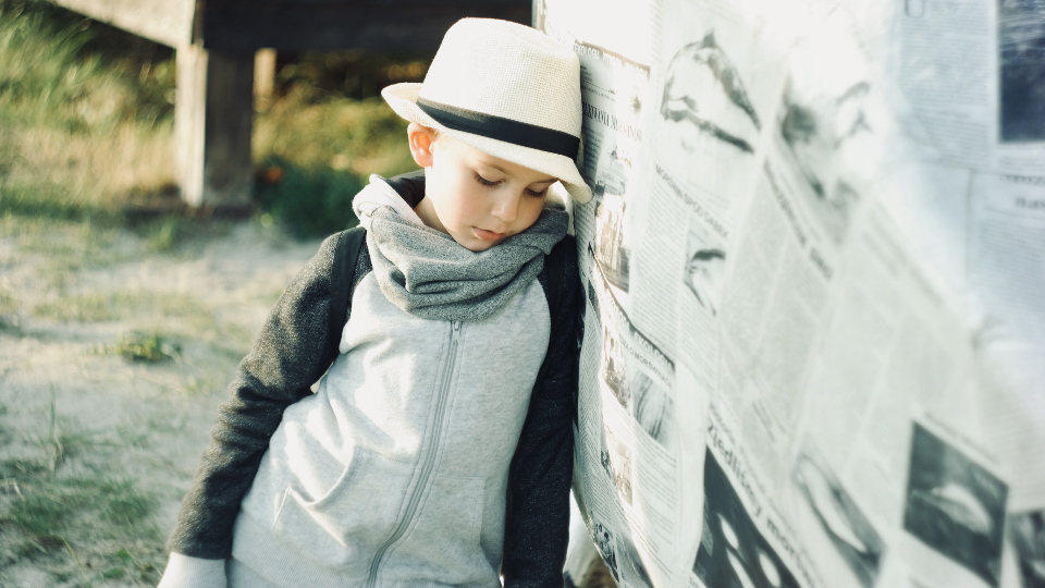 young child thinking pensive hat newspaper beach sand thoughful think