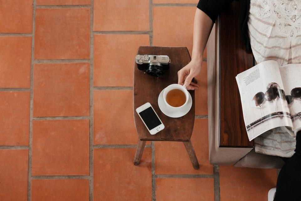 reading magazine people tea cup iphone mobile technology camera slr table tiles floor objects