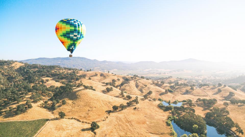 hot air balloon blue sky lake water mountain field outdoor nature trees