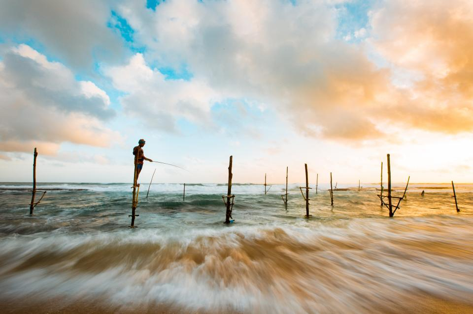 nature landscape water ocean sea waves splash wood stilts sticks person people stand fish sky clouds horizon
