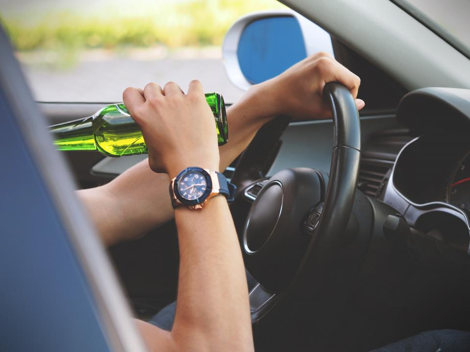alcohol automotive beer bottle opener car close-up control crime danger dangerous dashboard drink drive driver illegal odometer seat speedometer steering wheel transportation system travel vehicle watch