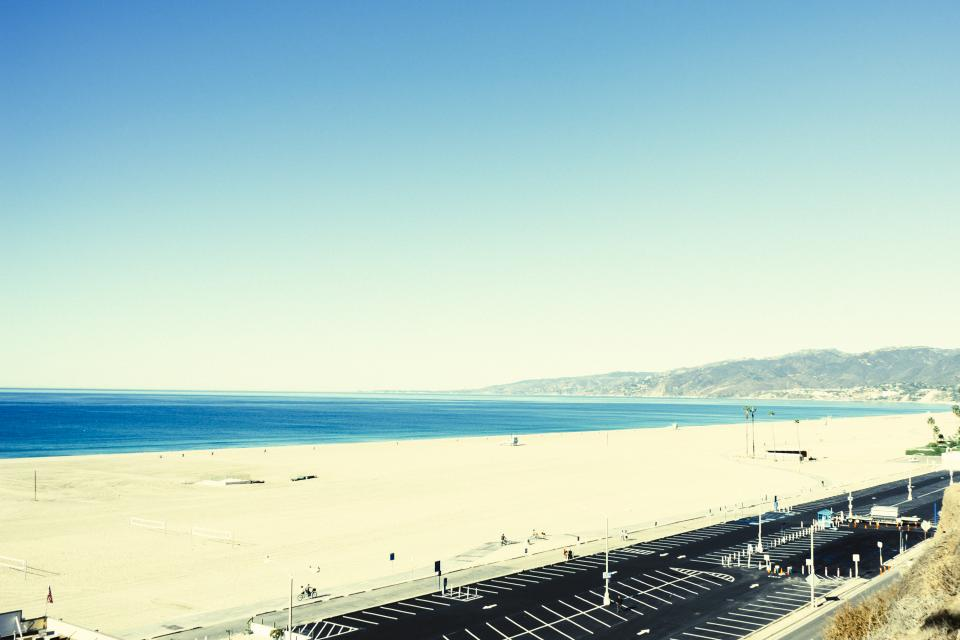 beach sand water ocean blue sky sunshine boardwalk parking lot mountains view