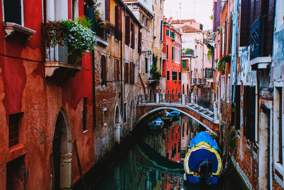 colorful buildings window flower plants boat river bridge pathway italy