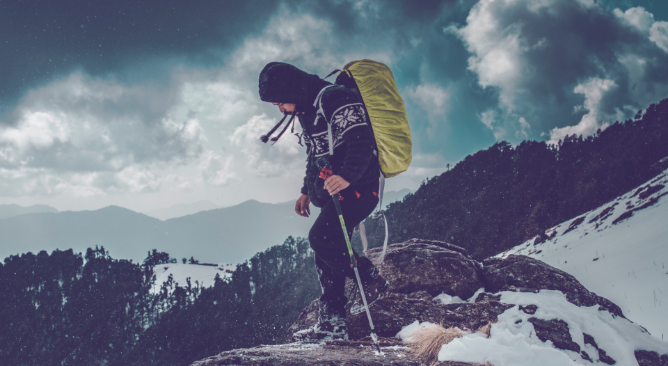 man hiking snow mountain hill winter cold frozen jacket backpack boots clouds dramatic scenery scenic landscape vista