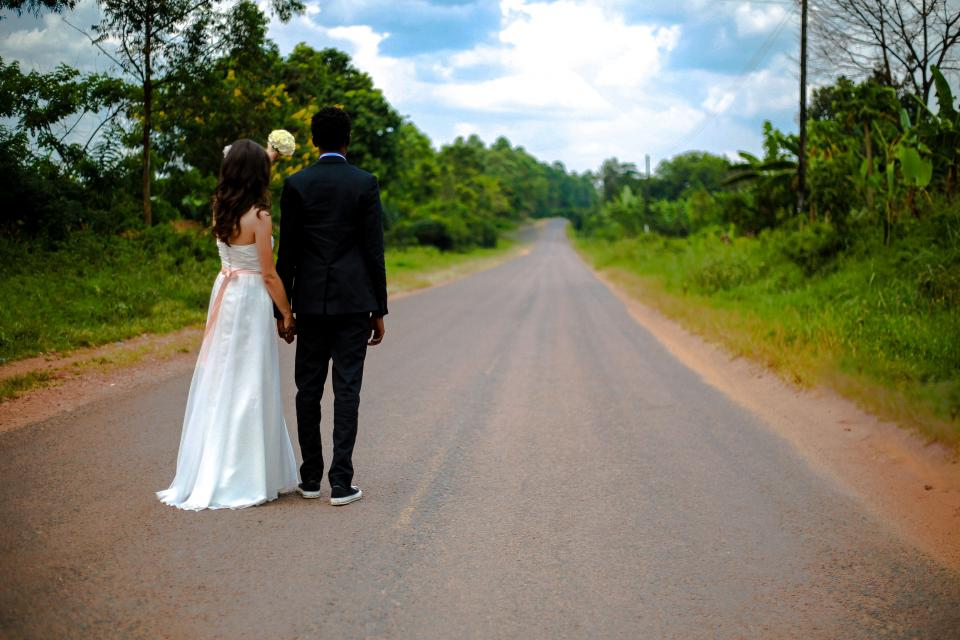 people couple man girl love wedding holding hands flower bouquet street road green grass trees sky clouds
