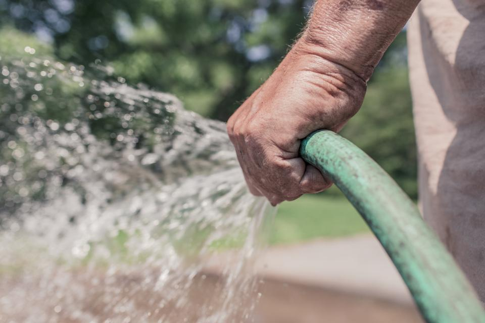garden hose gardener water spray hands