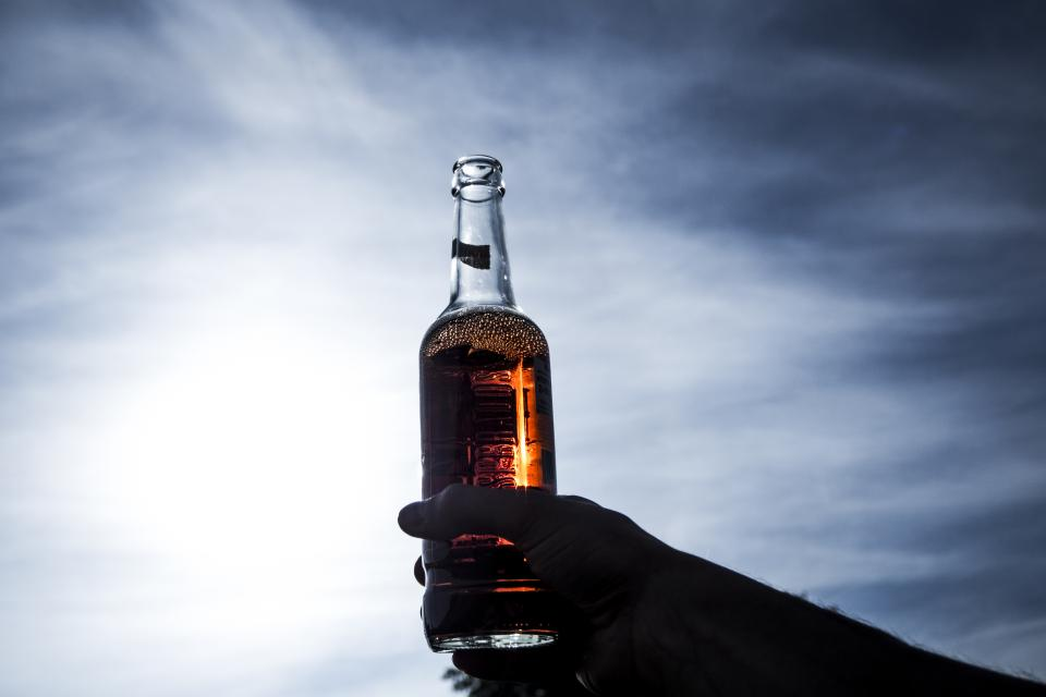 alcoholic drinks beer beverage bottle clouds dark daylight hand light liquor sky