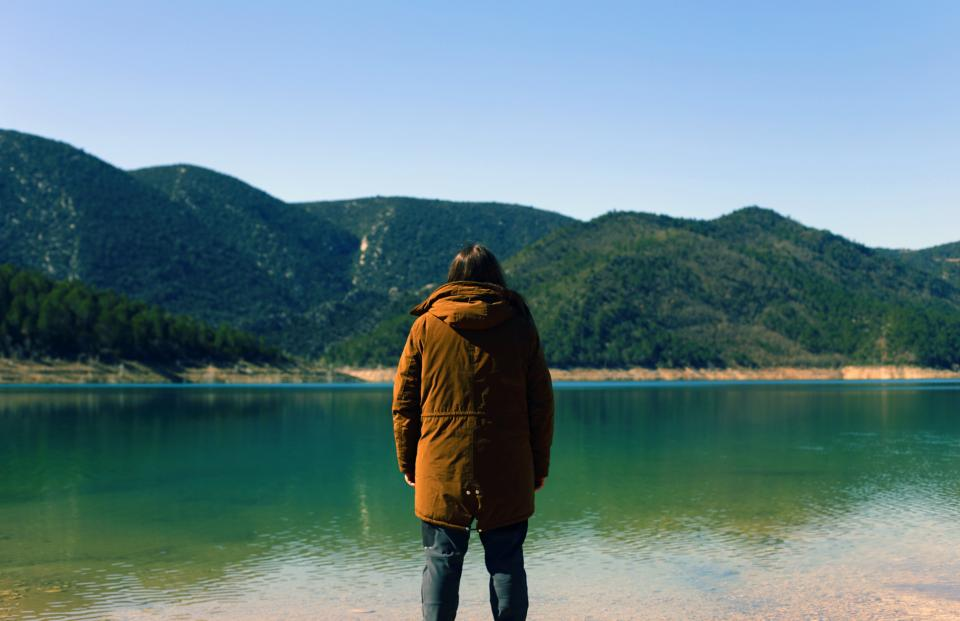 guy man male people back contemplate style hood coat view water lake surface still calm coast shore mountains lush vegetation sky picturesque