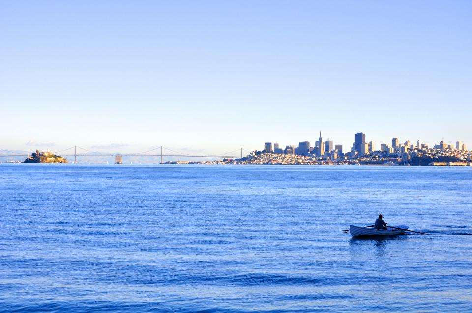 sky blue skyline san francisco golden gate bridge buildings water rowing boat