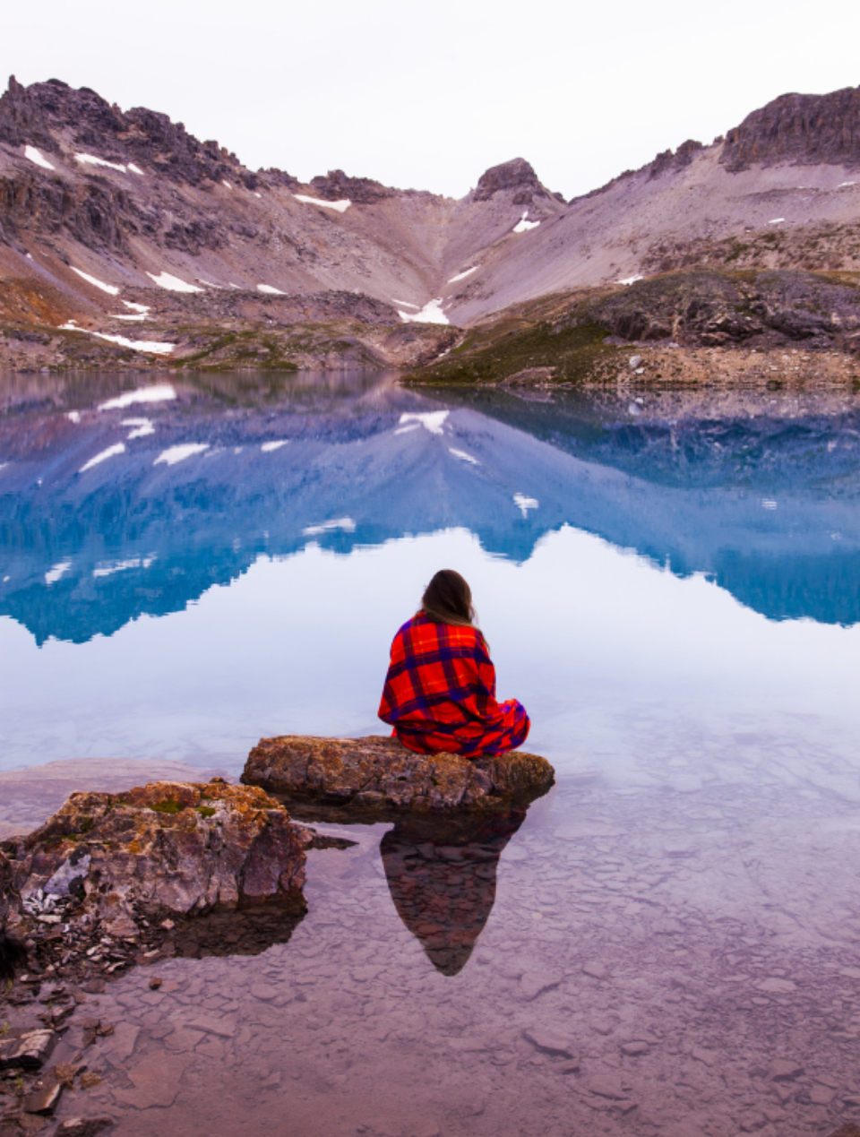 woman blanket lake cold frozen clear water river still rocks sit mountains people travel adventure