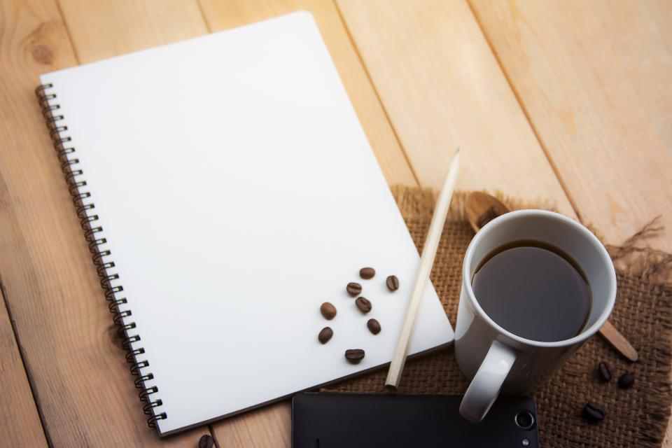 home desk coffee pencil beans notebook phone