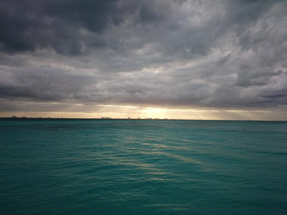sunbeams storm clouds cloudy sky grey water ocean sea landscape
