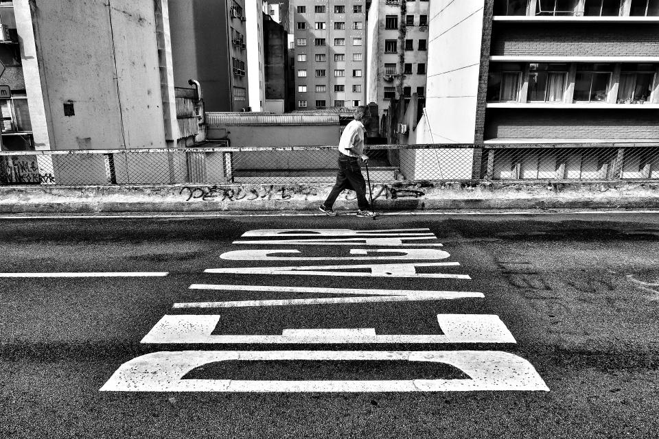 black and white building structure architecture road sidewalk people old man walking