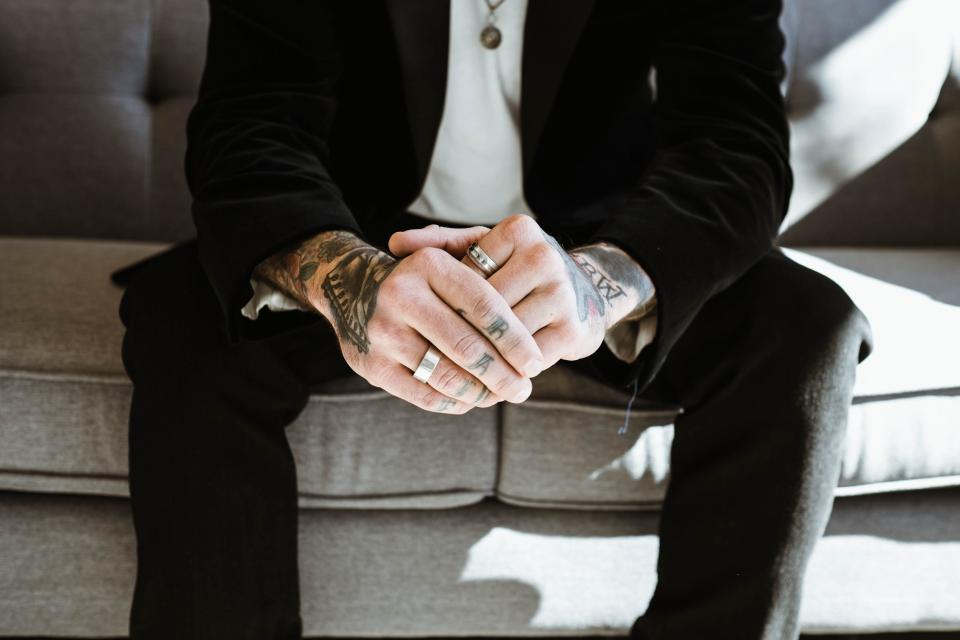 guy man rings hands fingers couch sofa sitting necklace tattoos sunlight black blazer