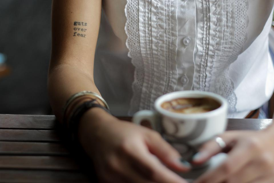people woman female blur coffee drink arm shoulder tattoo