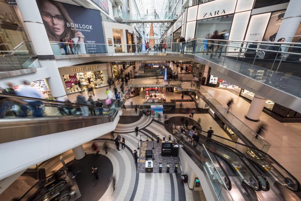 architecture building infrastructure shopping mall indoor inside escalator people crowd stores travel