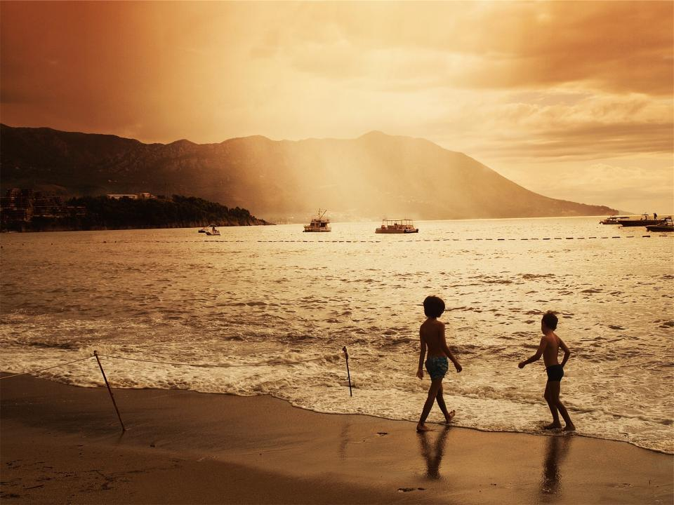 sunset dusk beach sand waves water ocean sea boats ships kids children playing people sky clouds mountains friends