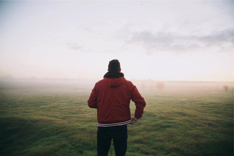 guy man jacket red hood grass field sky fog people