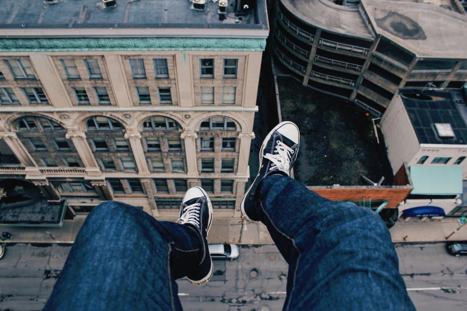 buildings city sneakers people edge rooftop travel