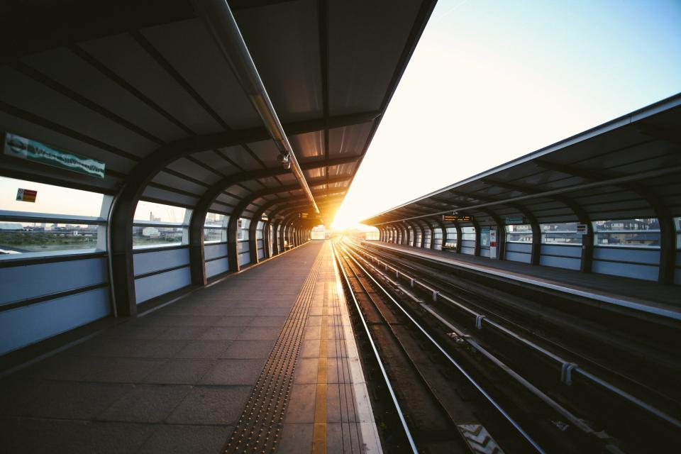 subway travel transport tracks sunlight sunrays sky cover architecture signs windows