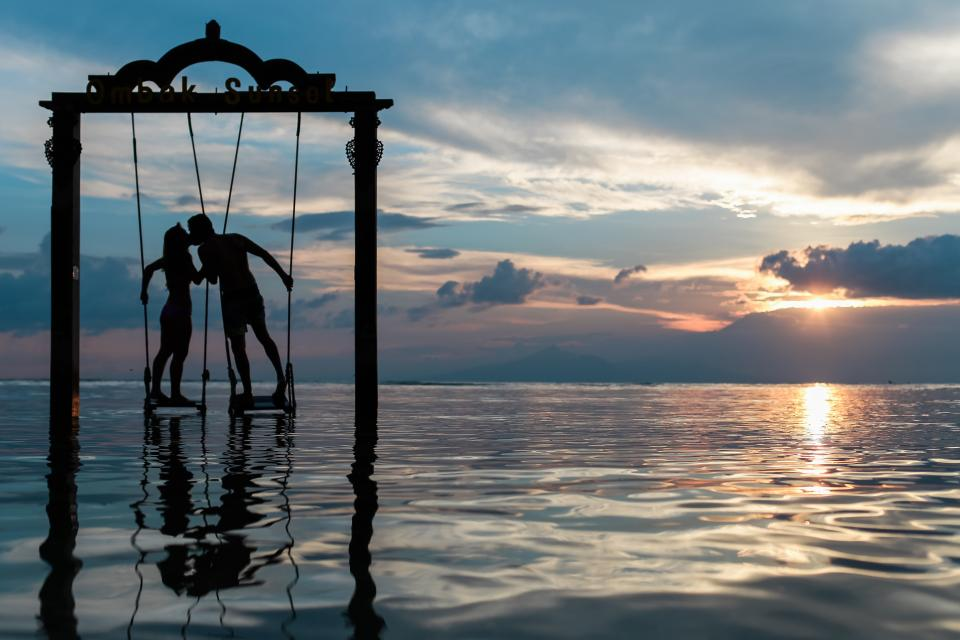 couple kissing love romance swing ocean sea sunset dusk silhouette clouds people