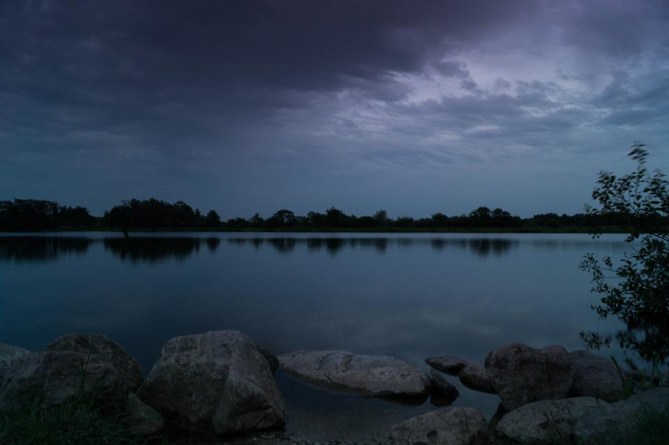 lake water dusk dark night trees rocks clouds cloudy sky