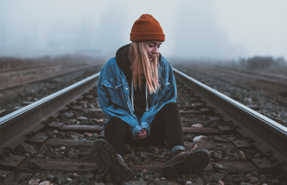 sitting train train tracks tracks girl blonde woman lady beanie cold weather cold weather foggy fog