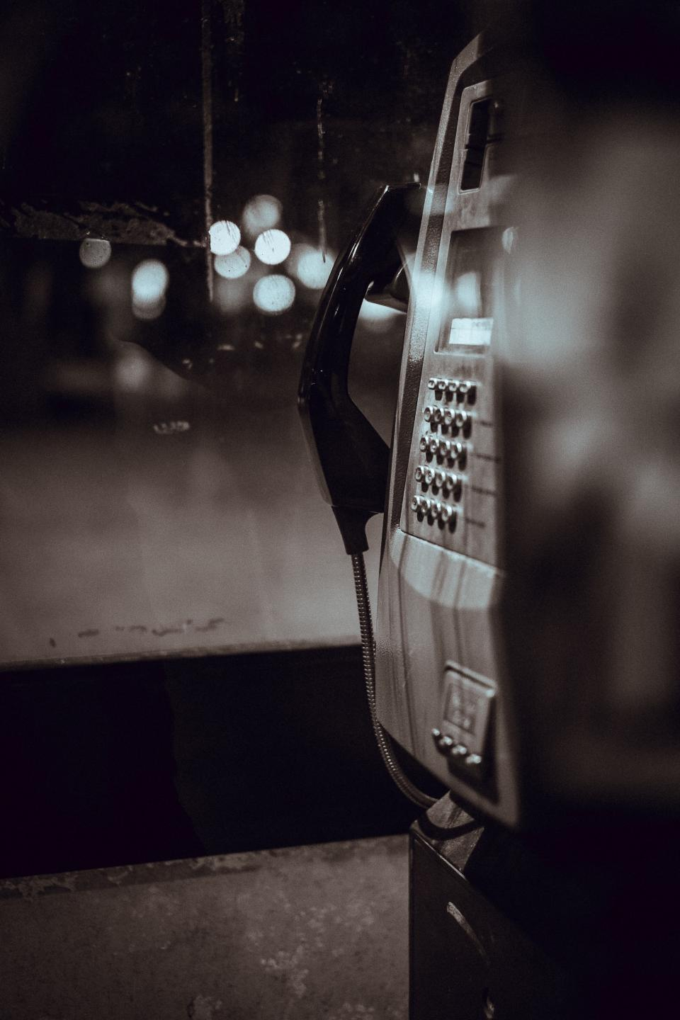 payphone communication call telephone black and white bokeh