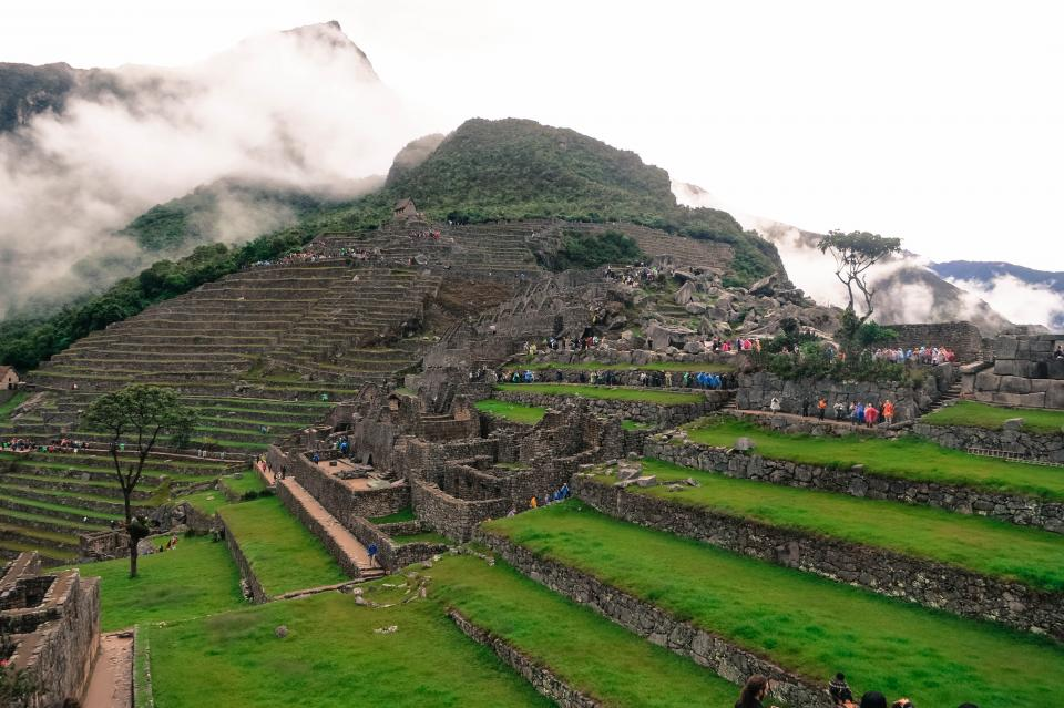 Machu Picchu Peru landscape green grass rocks people mountains clouds nature