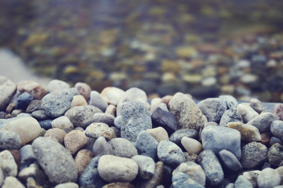 rocks pebbles beach clear water blue filter blur rocks