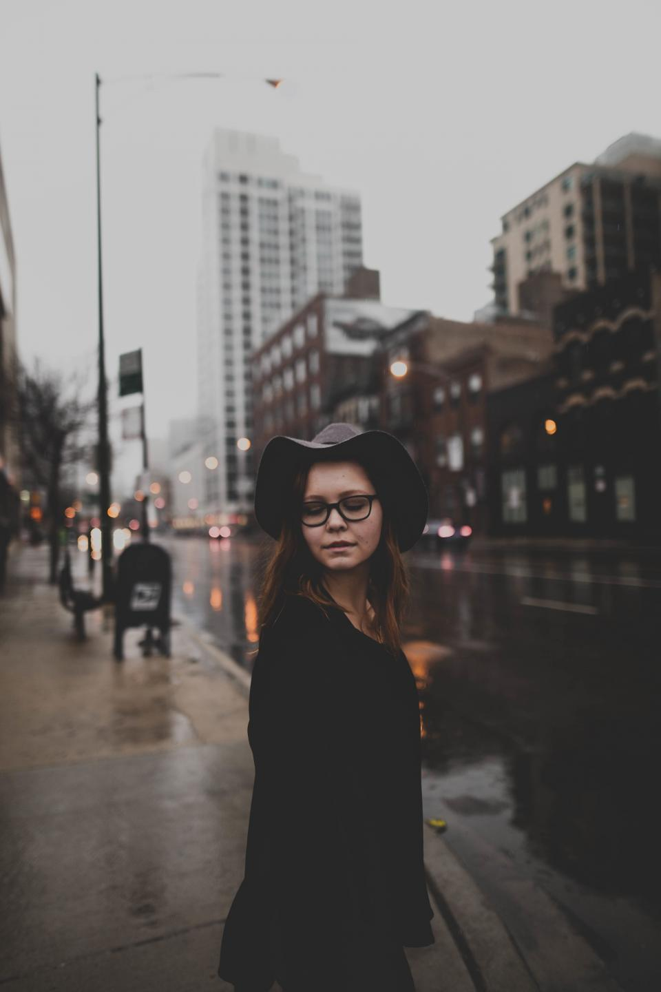people woman urban city street rain wet road establishment building store restaurant shop eyeglasses