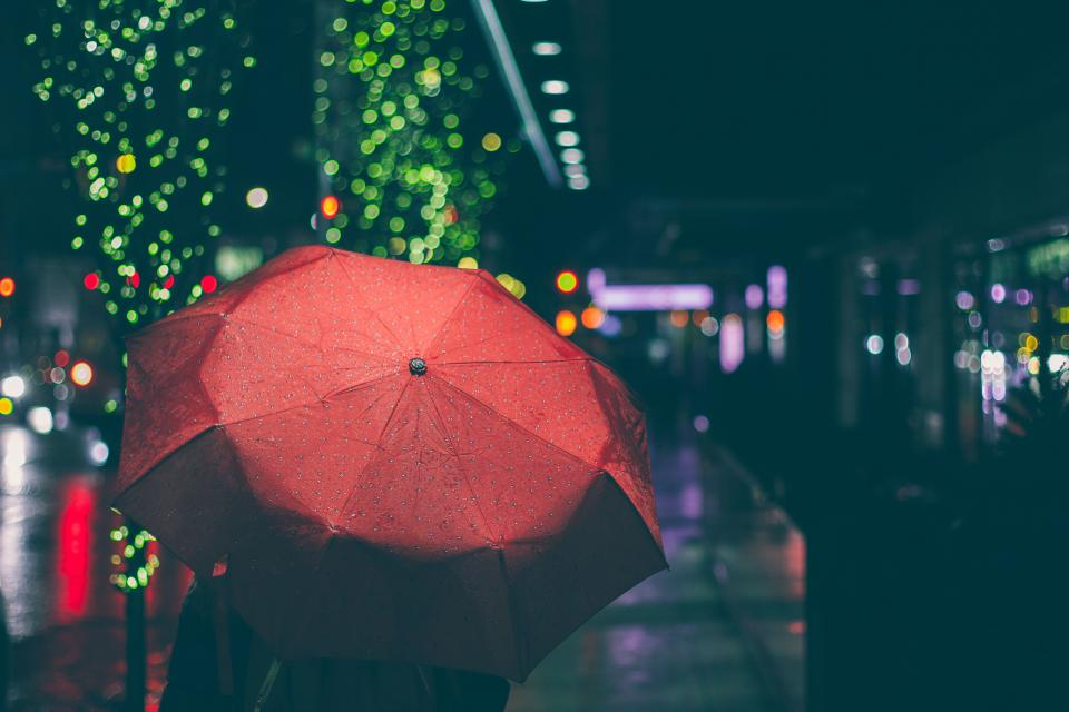 red umbrella raining night dark street city urban lights lifestyle
