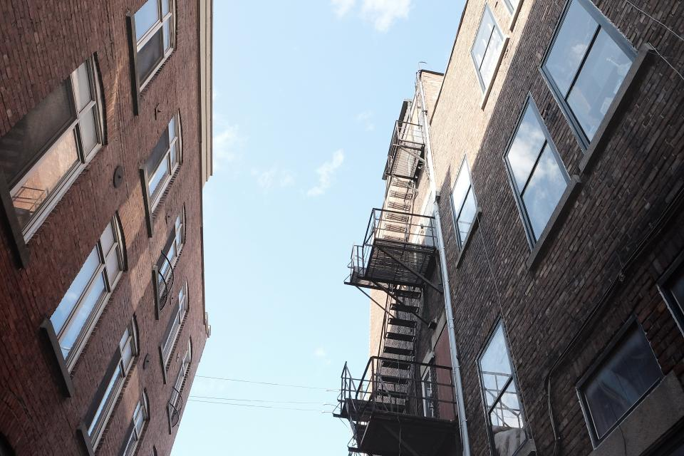 buildings houses apartments windows fire escape stairs steps ladders sky bricks walls