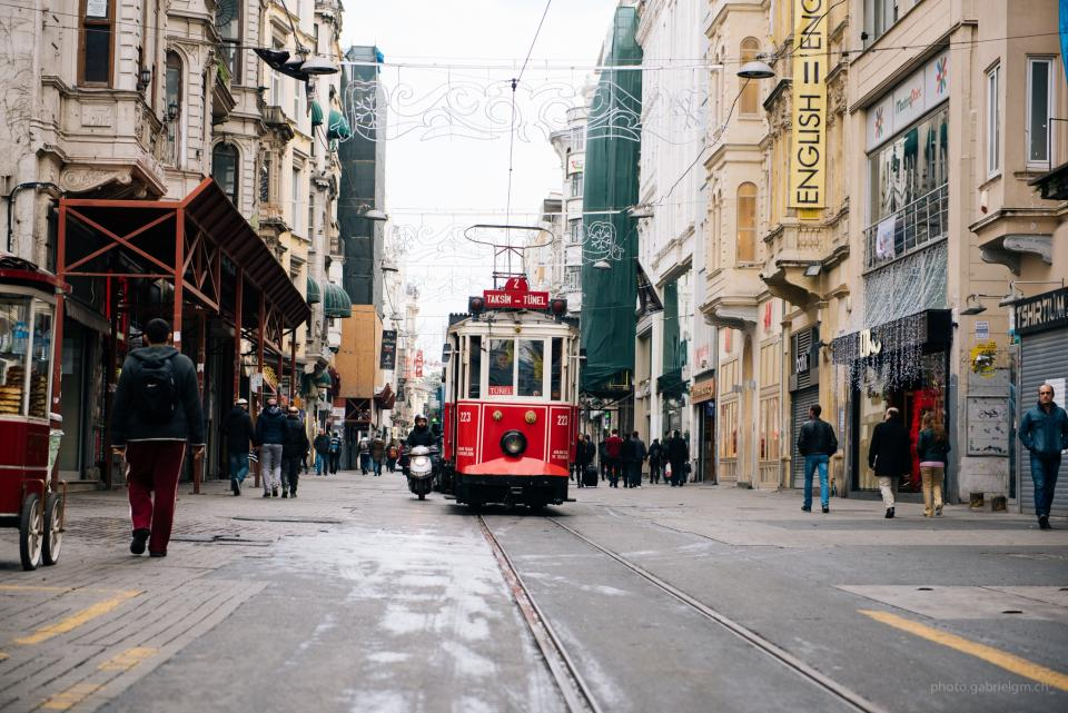 streetcar trolley streets city people pedestrians walking buildings stores shops architecture