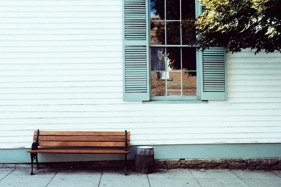 wood bench siding shutters window sidewalk
