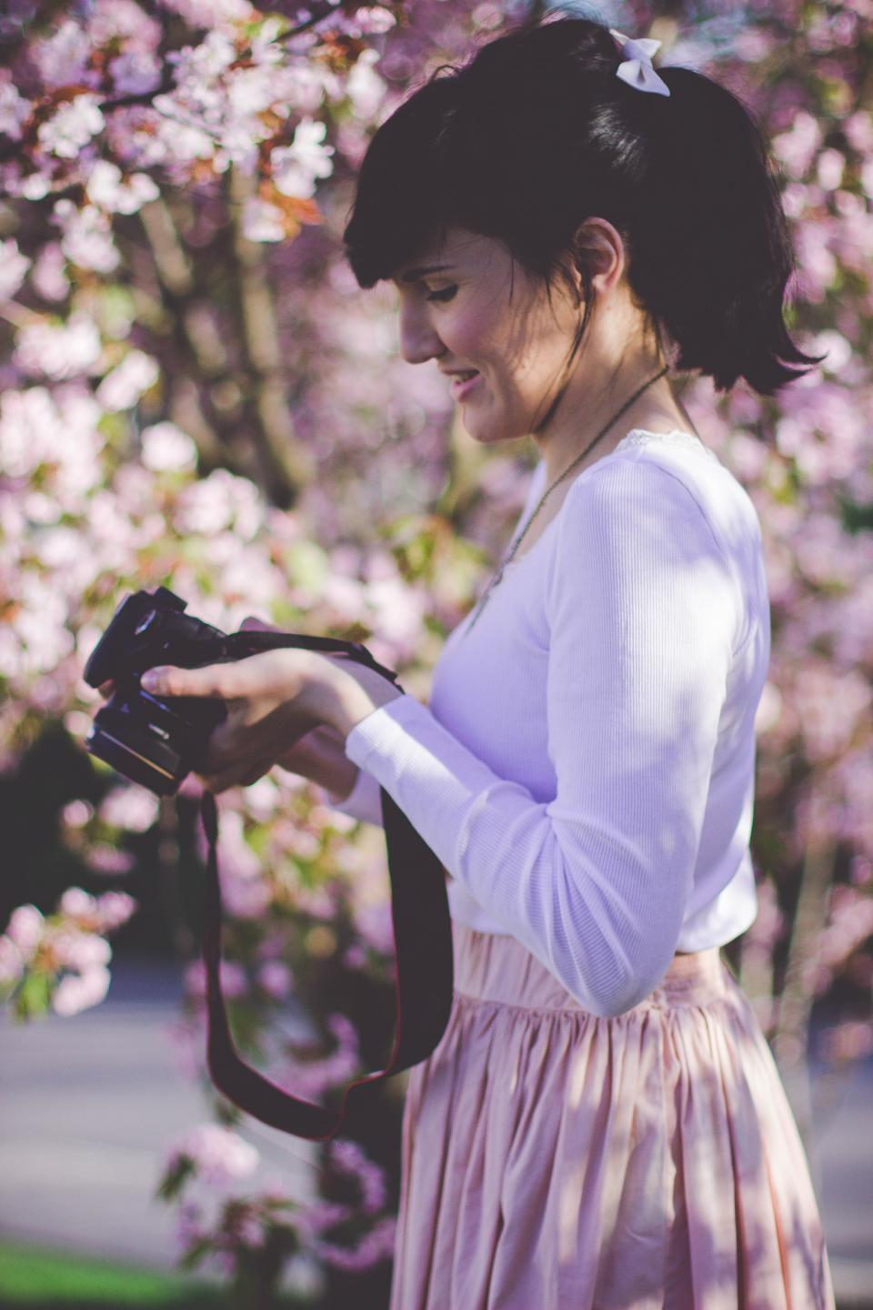 people girl woman alone fashion clothing nature plant outdoor flowers petal bokeh blur camera photographer smile happy travel