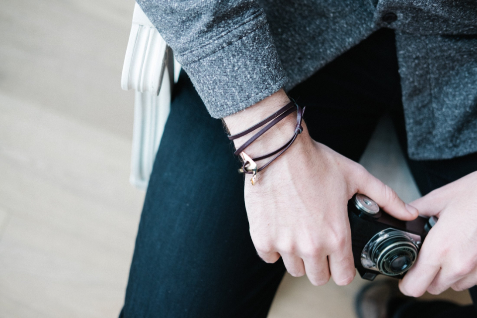 hands camera close up bracelet photographer holding person equipment casual fashion lens film journalist professional hobby