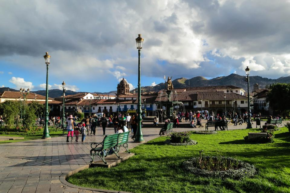 Plaza de Armes Cusco Peru lamp posts benches grass path people pedestrians crowd buildings town